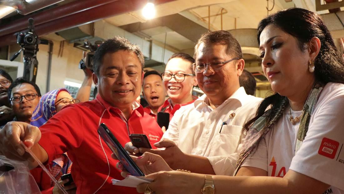 Menkominfo Rudiantara (tengah) didampingi oleh Direktur Utama Telkomsel Ririek Adriansyah (kiri) dan Direktur PT Mikrobisnis Debbie Sianturi (kanan) saat mencoba Snap QR Code dari TCASH di Pasar Modern Mayestik, Jakarta Selatan.