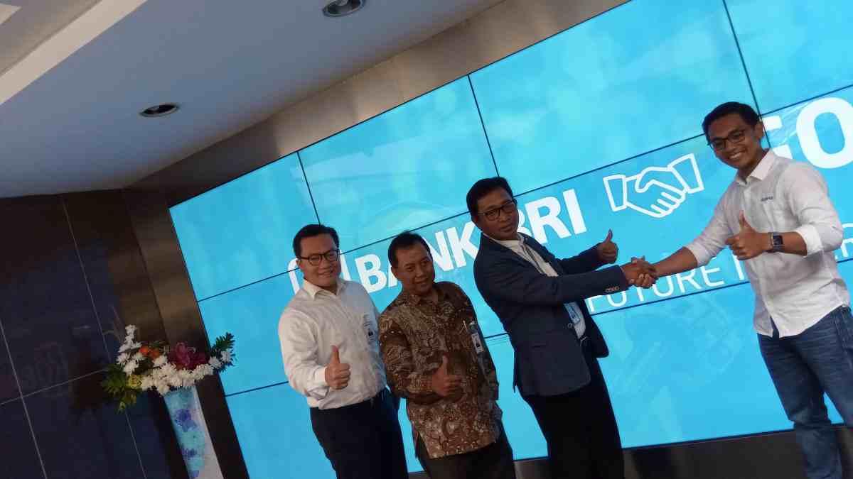 Direktur Hubungan Kelembagaan BRI, Sis Apik Wijayanto (dua dari kanan), dan CEO GO-PAY, Aldi Haryopratomo (paling kanan), berjabat tangan usai menandatangani nota kesepahaman antara GO-PAY dan BRI.